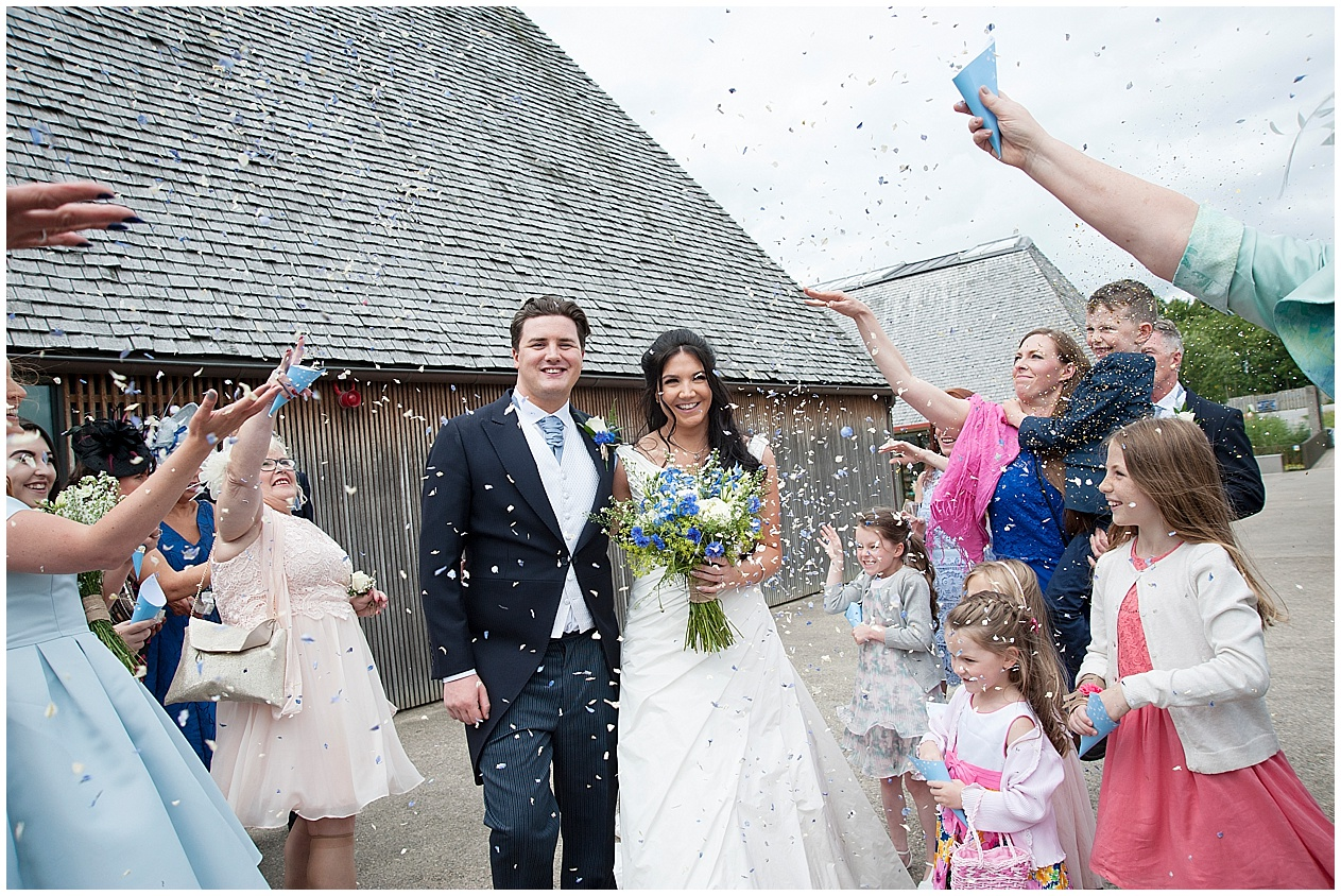 Guests throw confetti at a bride and groom at their wedding at Brockholes nature reserve in Preston.