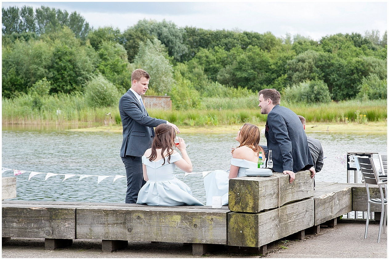 Guests enjoy a drink on the jetty at a wedding at Brockholes nature reserve in Preston.