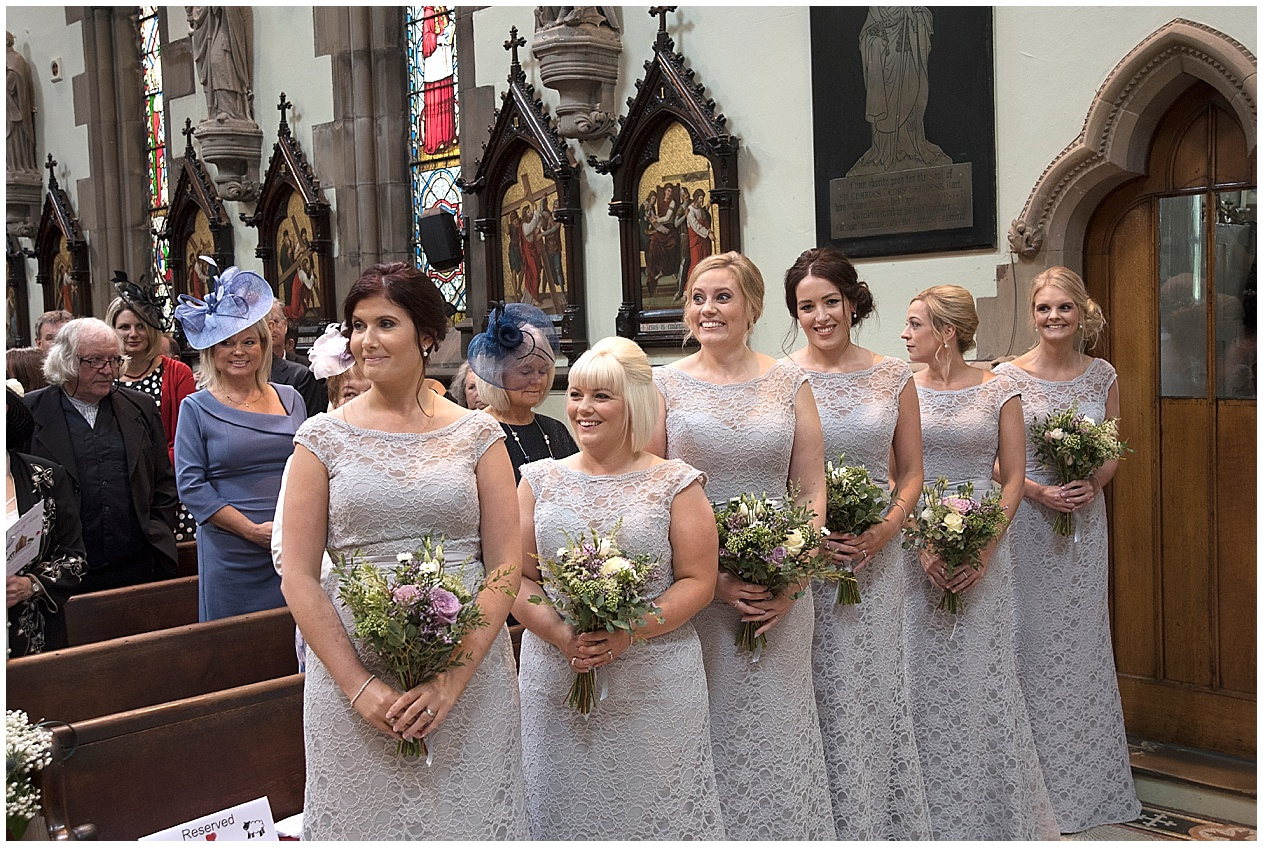 Bridesmaids watch as the bride walks down the aisle with her father. Lancashire wedding photographer.