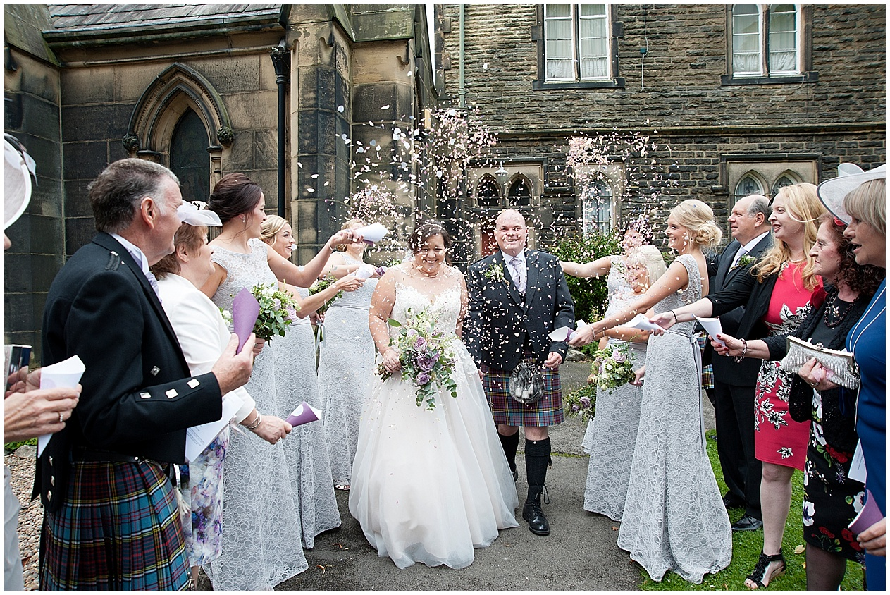 Guests throw confetti at the bride and groom on their wedding day. Stirk House wedding photography.