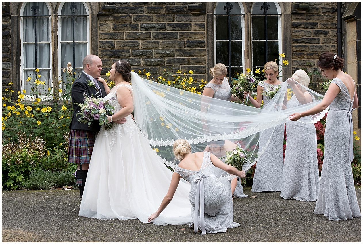 Bridesmaids adjust the brides dress and veil ready for photographs. Lancashire wedding photographer.