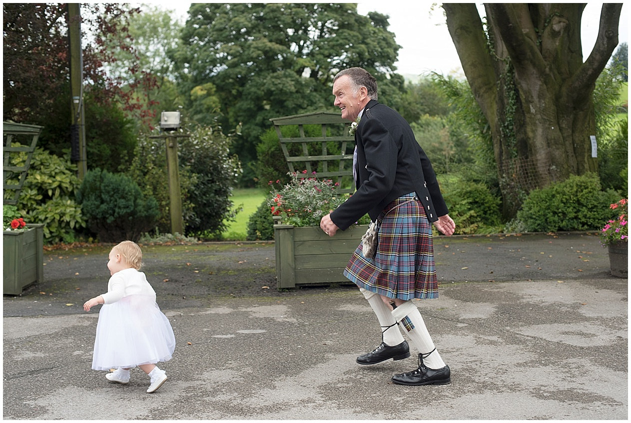 father of the groom chases after his grand daughter at a wedding at Stirk House in Lancashire.