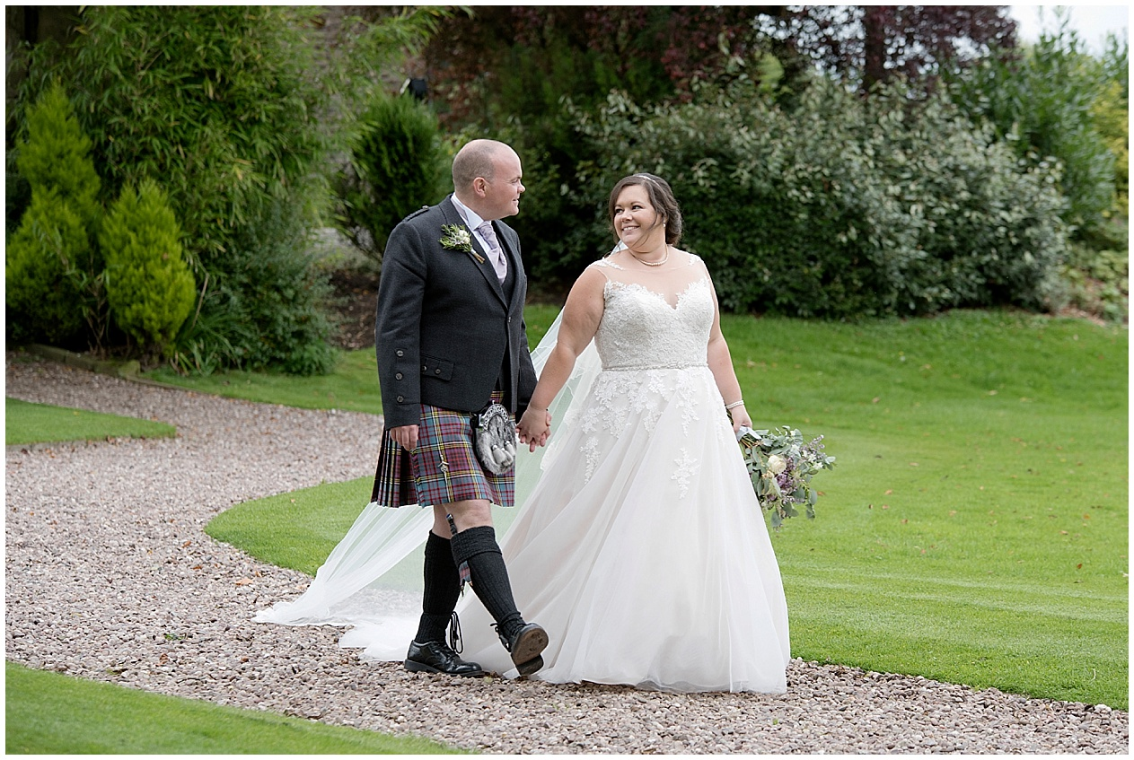 Bride and groom take a stroll around the grounds at Stirk House. Strike House wedding photography