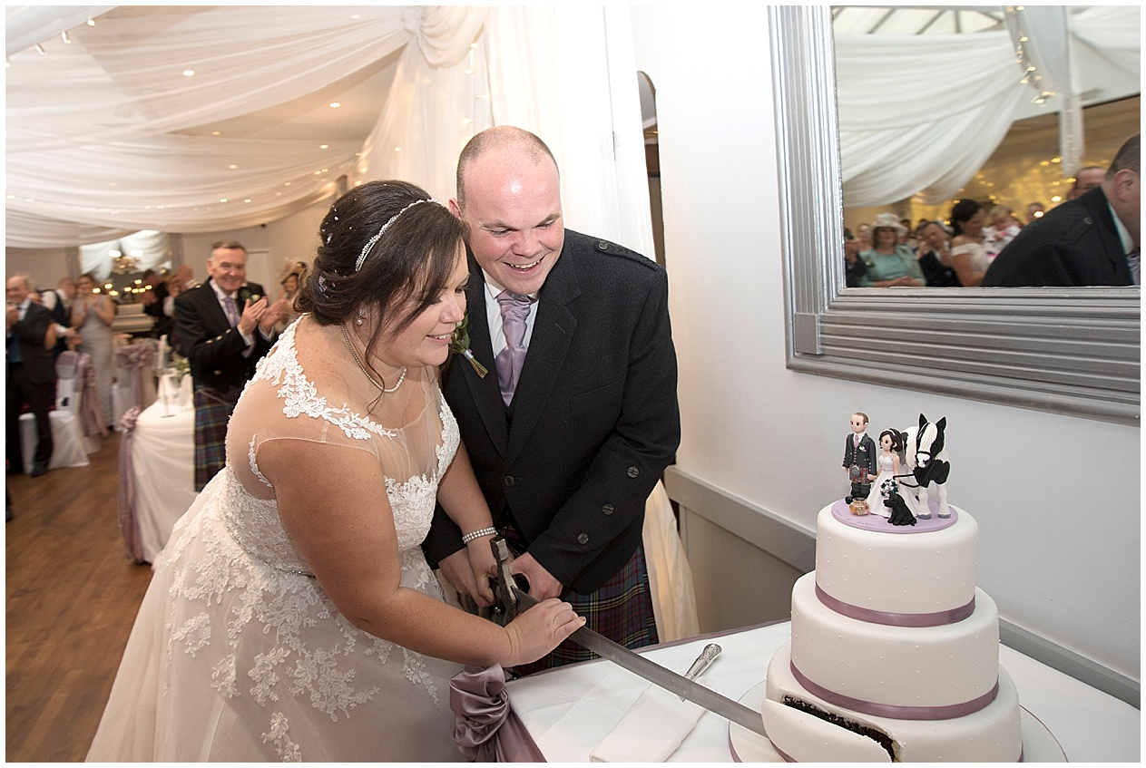Bride and groom cut their wedding cake with a sword.