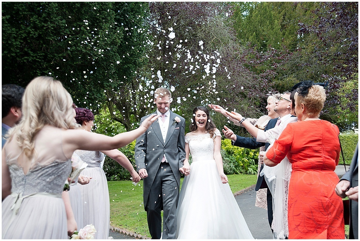 Guests throw confetti at a bride and groom on their wedding day.