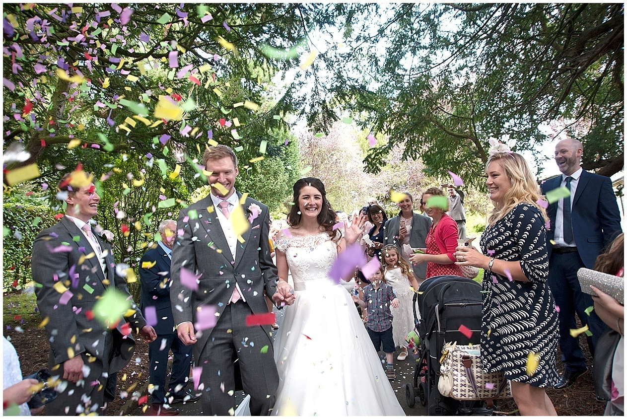 Bride and groom get covered with confetti. Harrogate wedding photographer.