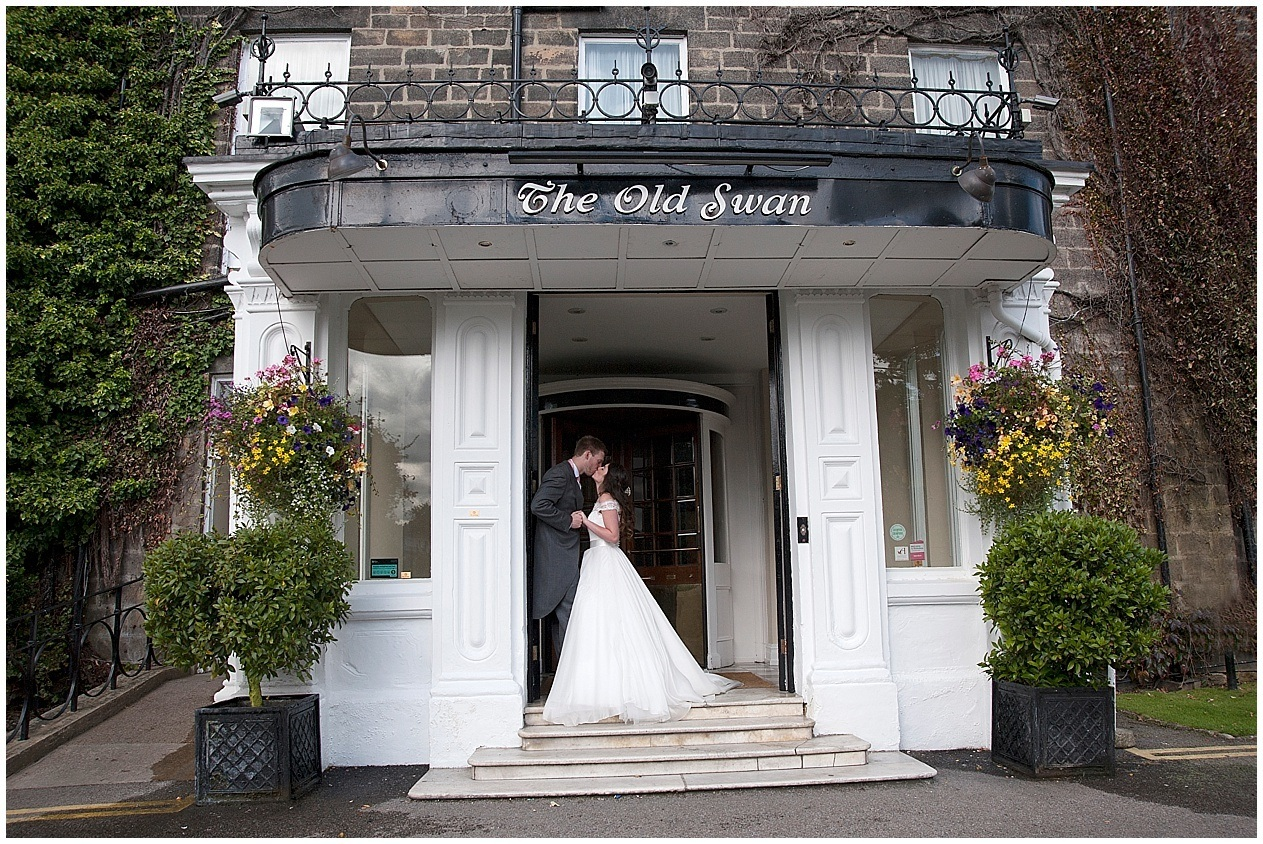 The Old Swan Hotel in Harrogate wedding photography. The bride and groom share a kiss in the hotel doorway.