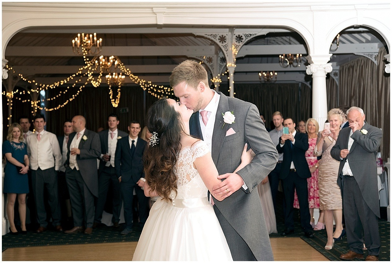 Bride and groom share a kiss on the dance floor at their wedding in Harrogate