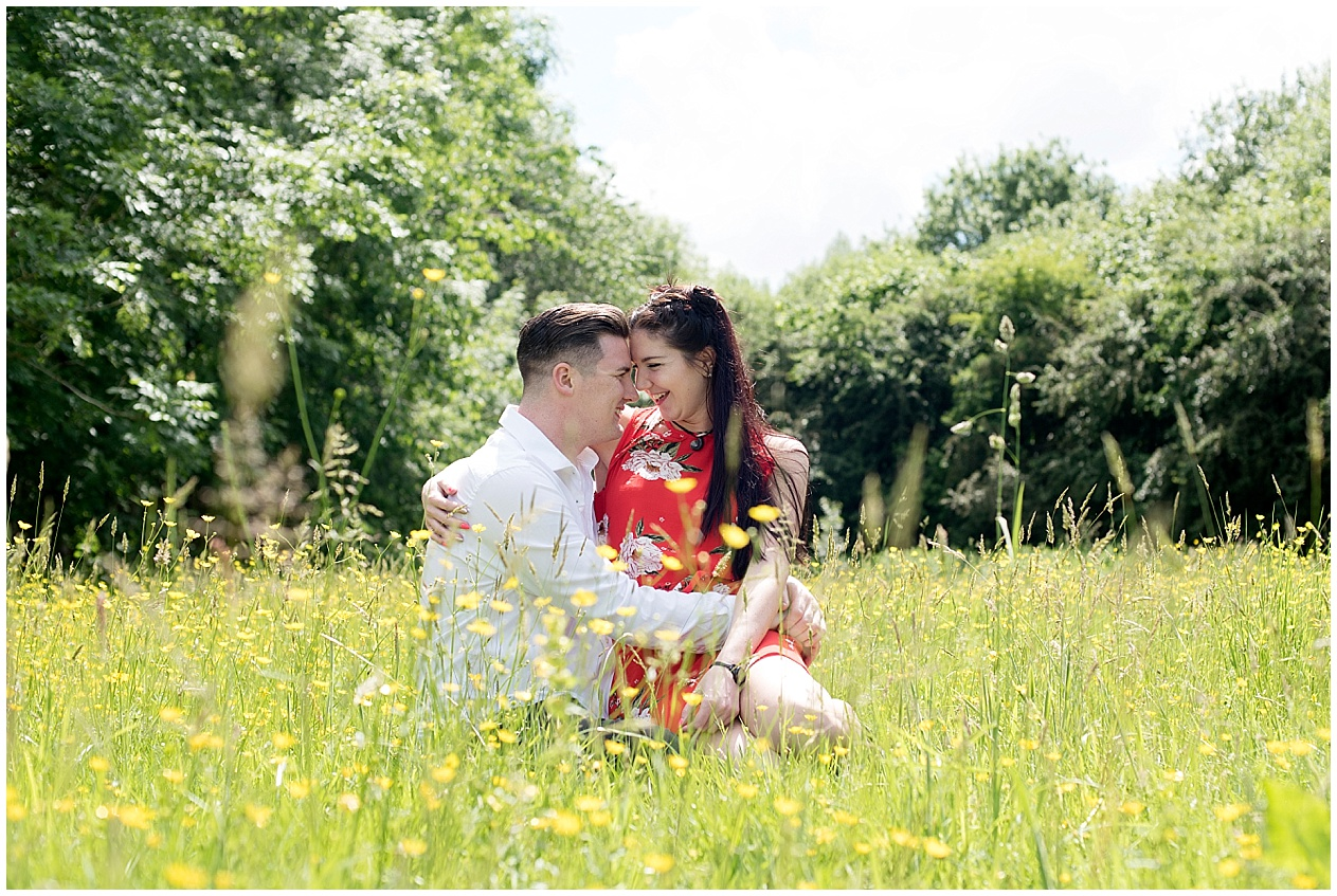 Preston wedding photographer. A couple sit amongst the buttercups on their pre wedding photoshoot at Brockholes nature reserve.