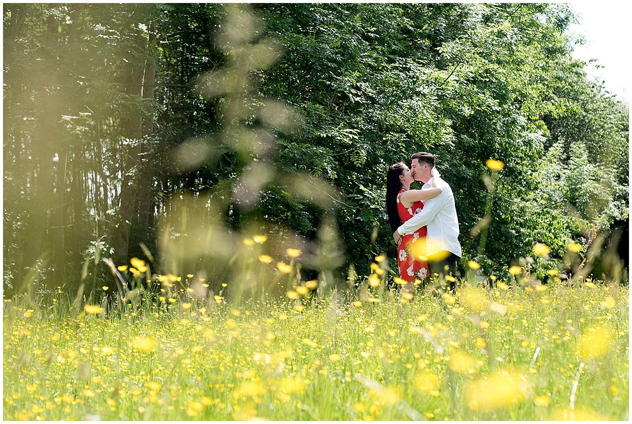 Lancashire wedding photographer. A young couple kiss in a buttercup meadow in the Lancashire countryside.