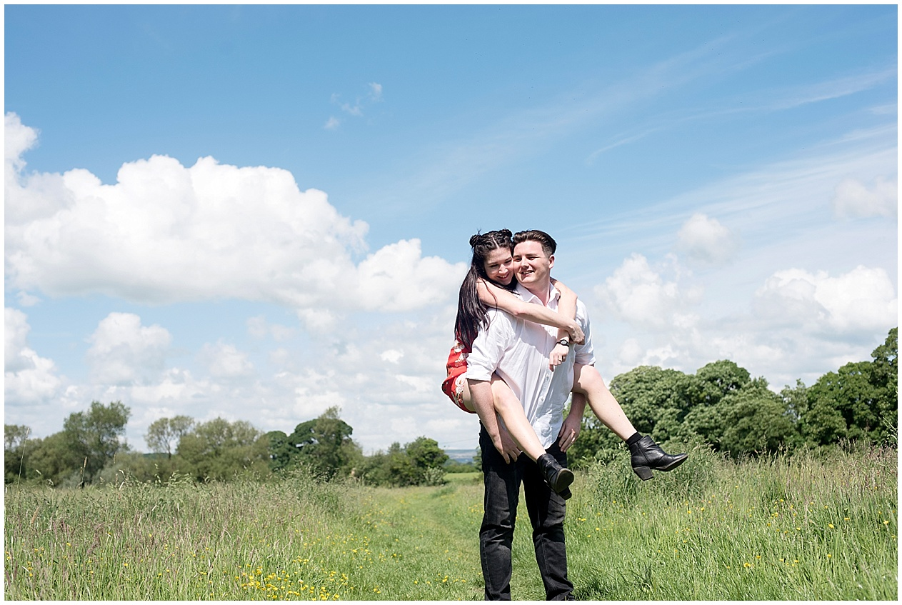A girl gets a piggy back from her husband to be during their engagement photoshoot at Brockholes nature reserve in Preston.