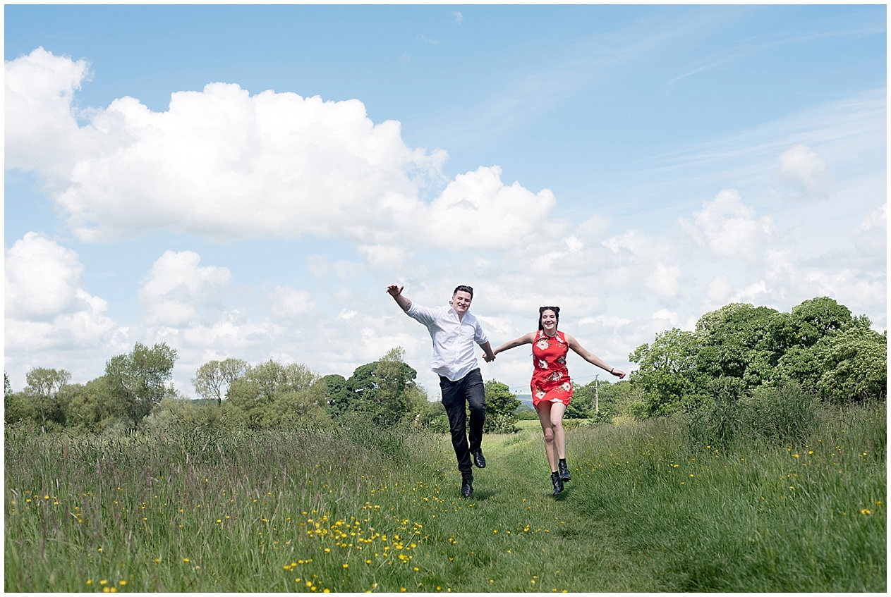 A  young couple skip through a summer meadow in Lancashire. Lancashire wedding photographer.