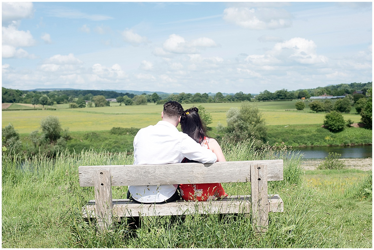 A couple sit on a bench looking out over the lancashire countryside on a summers day.