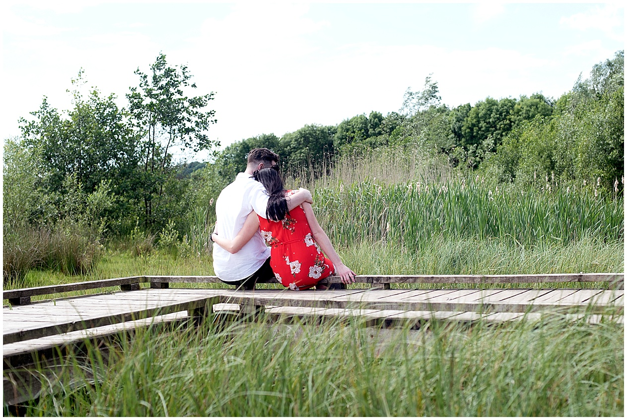 A young couple sit amongst the reeds on their engagement photography session at Brockholes nature reserve. Preston wedding photographer