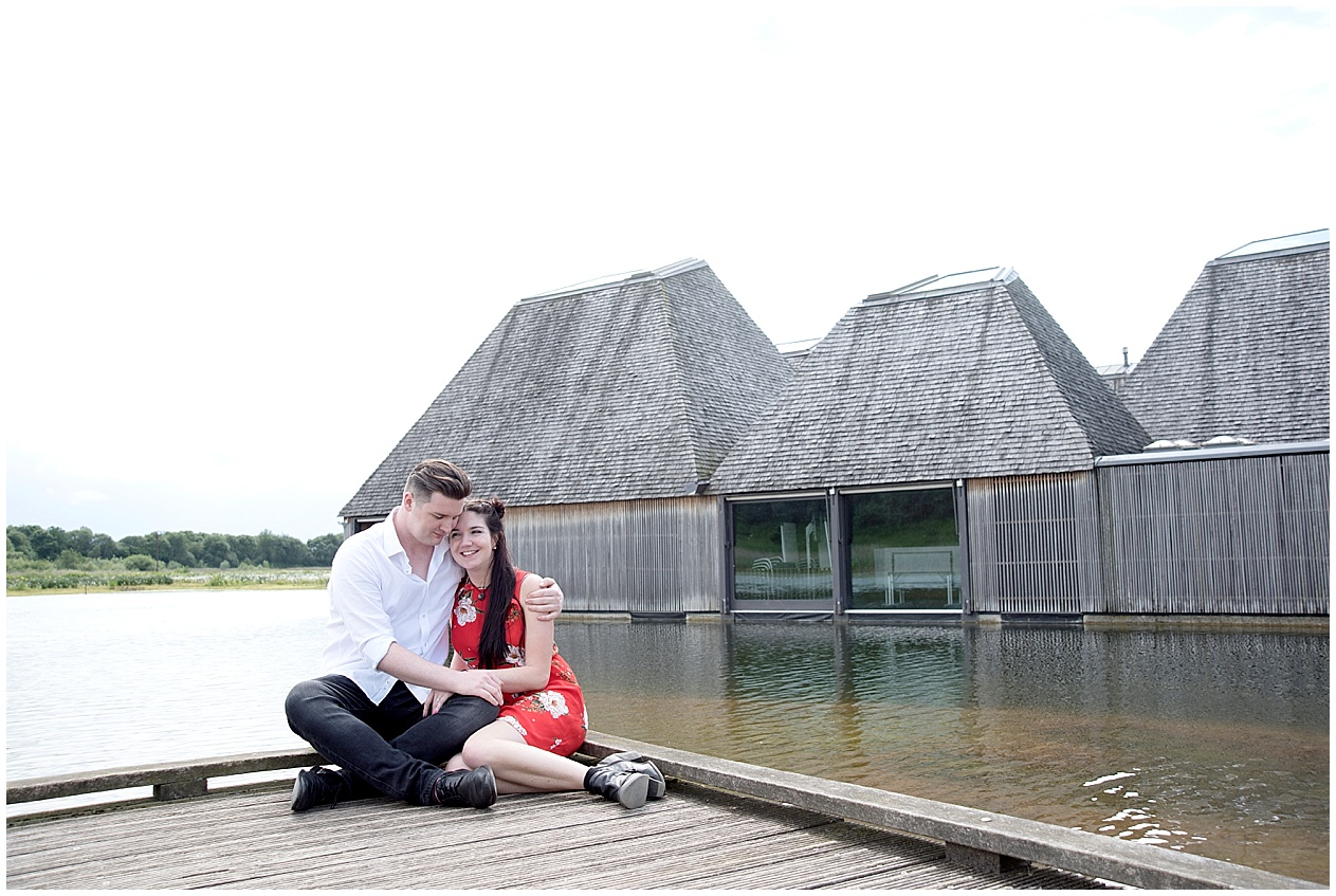 Brockholes nature reserve engagement photoshoot. couple sit by the floating village.