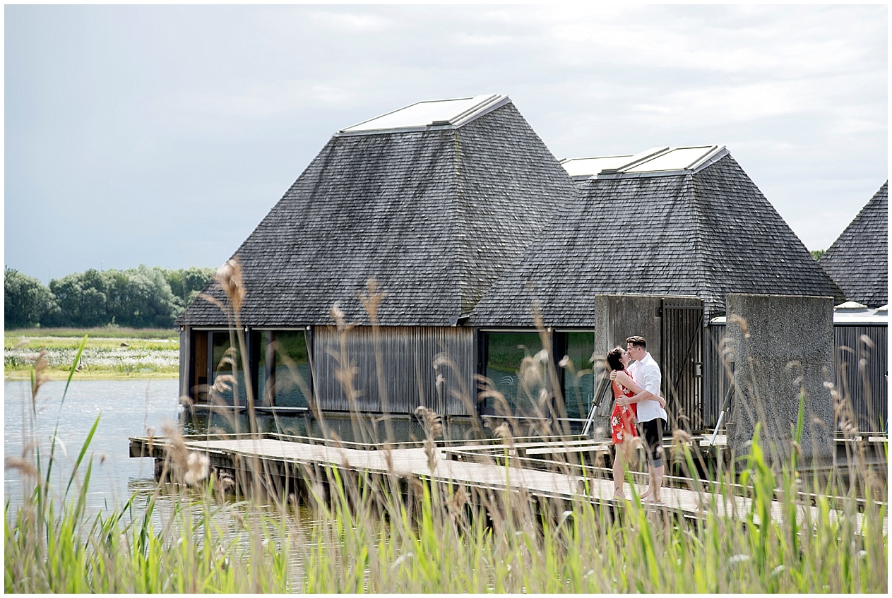 A couple pictured by the floating village at Brockholes nature reserve on their engagement photoshoot. Preston wedding photographer.