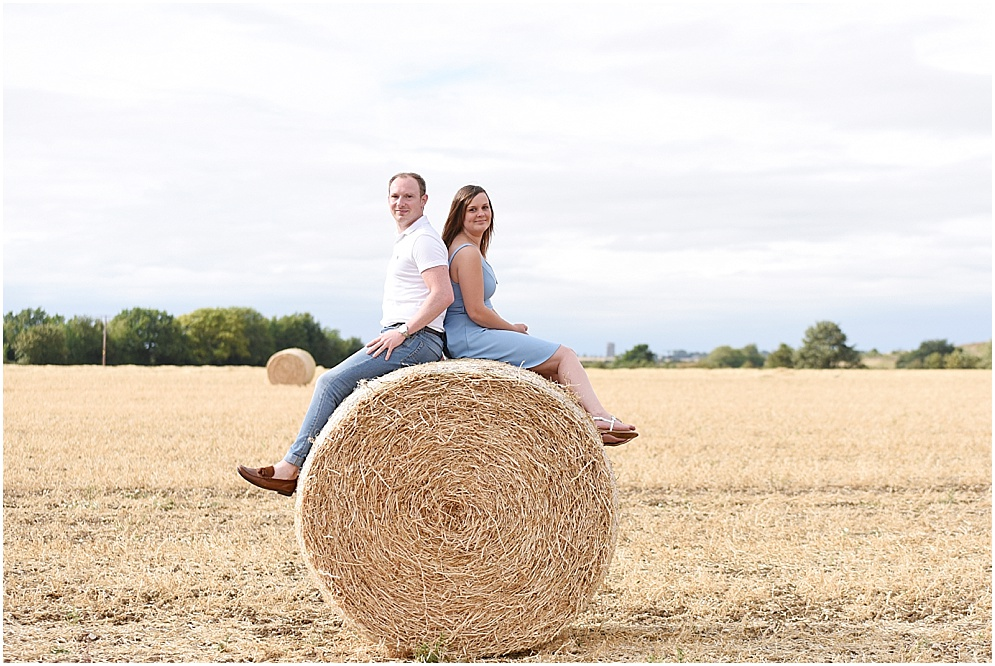 Bride and groom sit on a hay bale during their engagement session. Hitchin wedding photographer at Oughthead common.