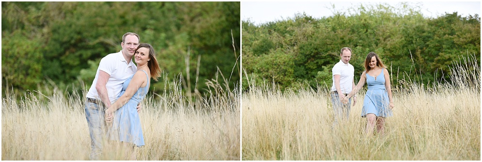 A couple walk through some long grass on a summers day during their pre wedding photoshoot at Oughtonhead common in Hertfordshire. Hitchin wedding photography