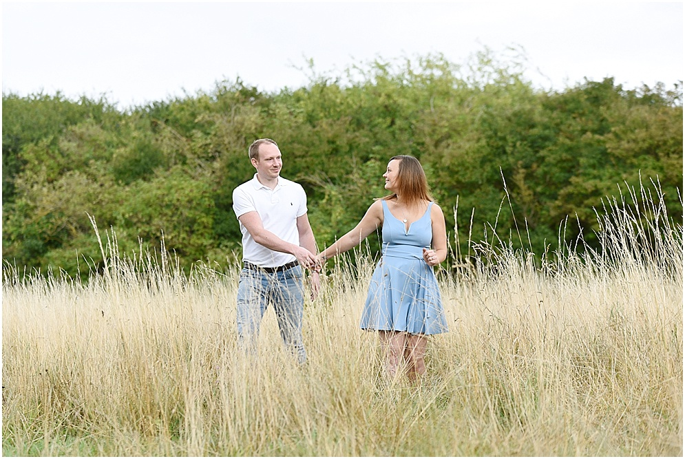 Bride and groom walk through the long grass on their pre wedding shoot at Oughtonhead common. Hitchin wedding photographer