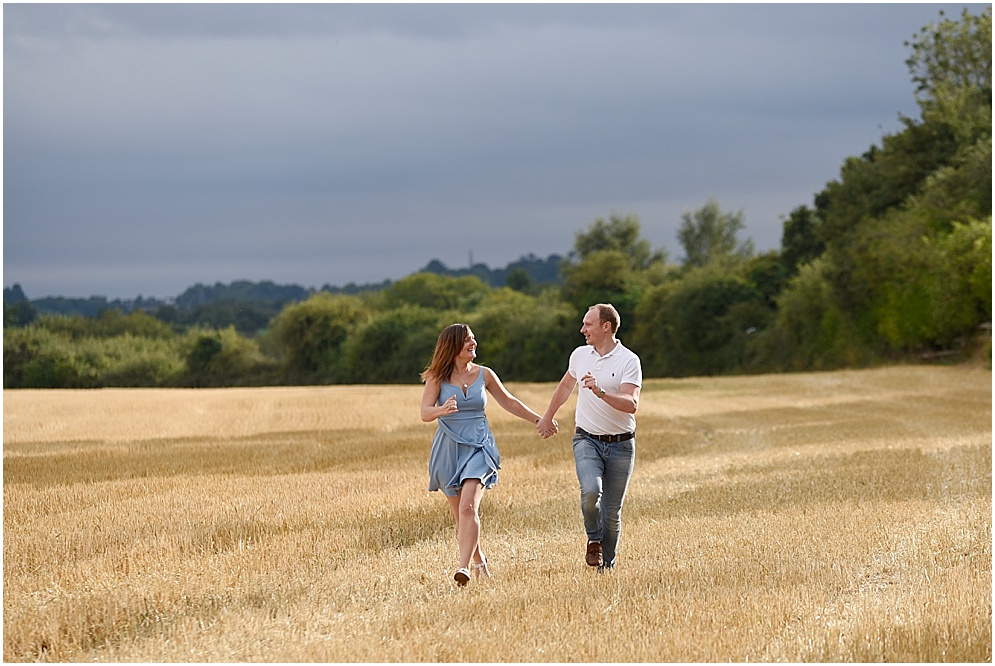 Hitchin wedding photographer, a bride and groom run across a corn field on their engagement shoot
