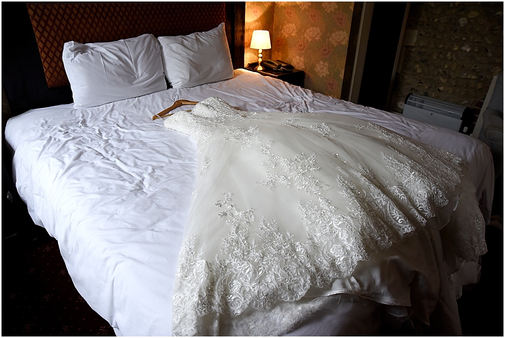 Wedding dress pictured lying on a bed.
