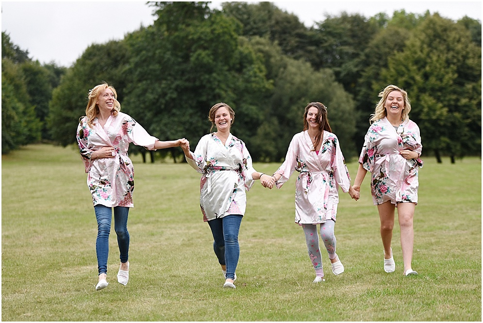 Bride and her bridesmaids walk across the lawn at Hitchin Priory. Hitchin Priory wedding photography.