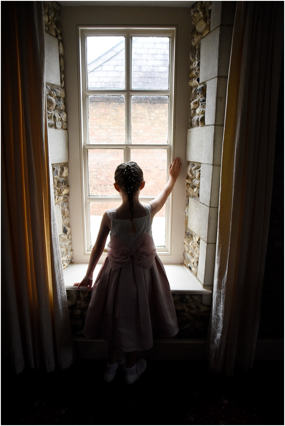Flower girl looks out of the window.