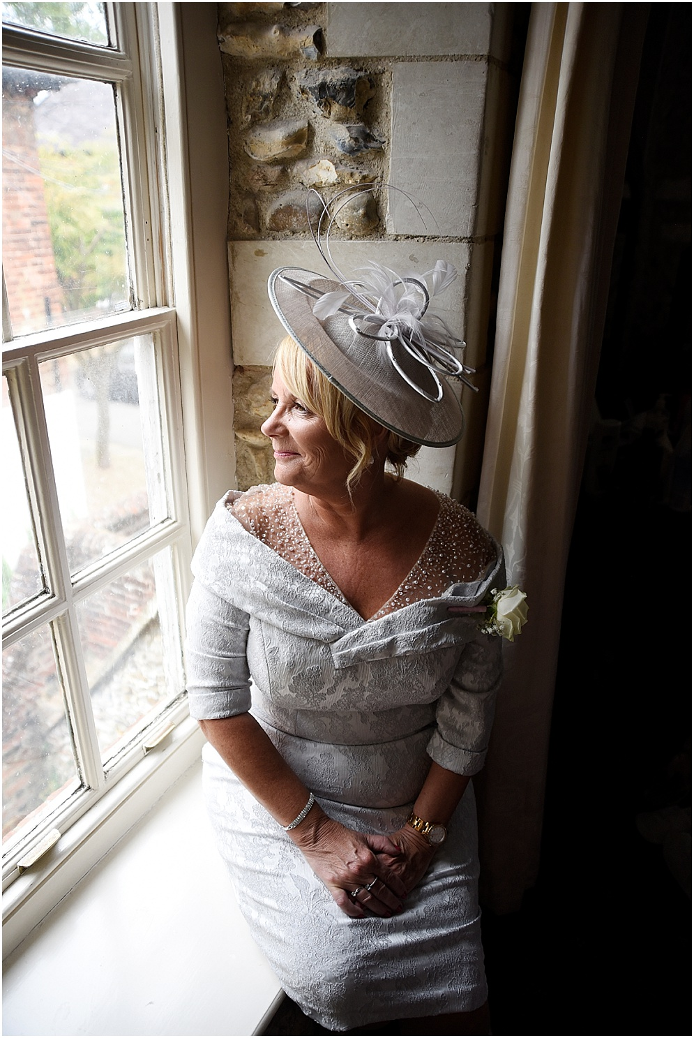 Mother of the bride looks out of the window at Hitchin Priory.