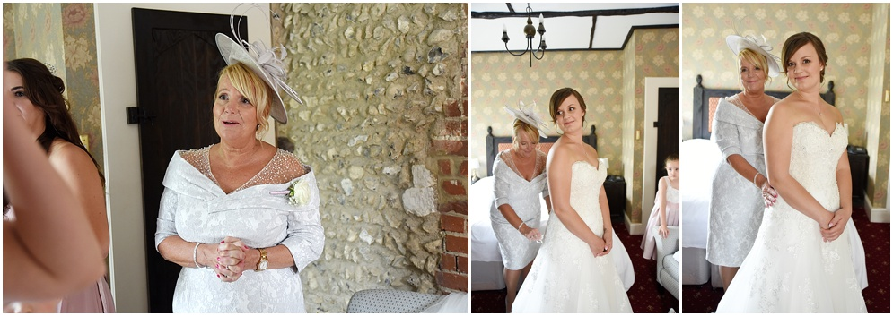 Mother of the bride helps her daughter get her wedding dress on.