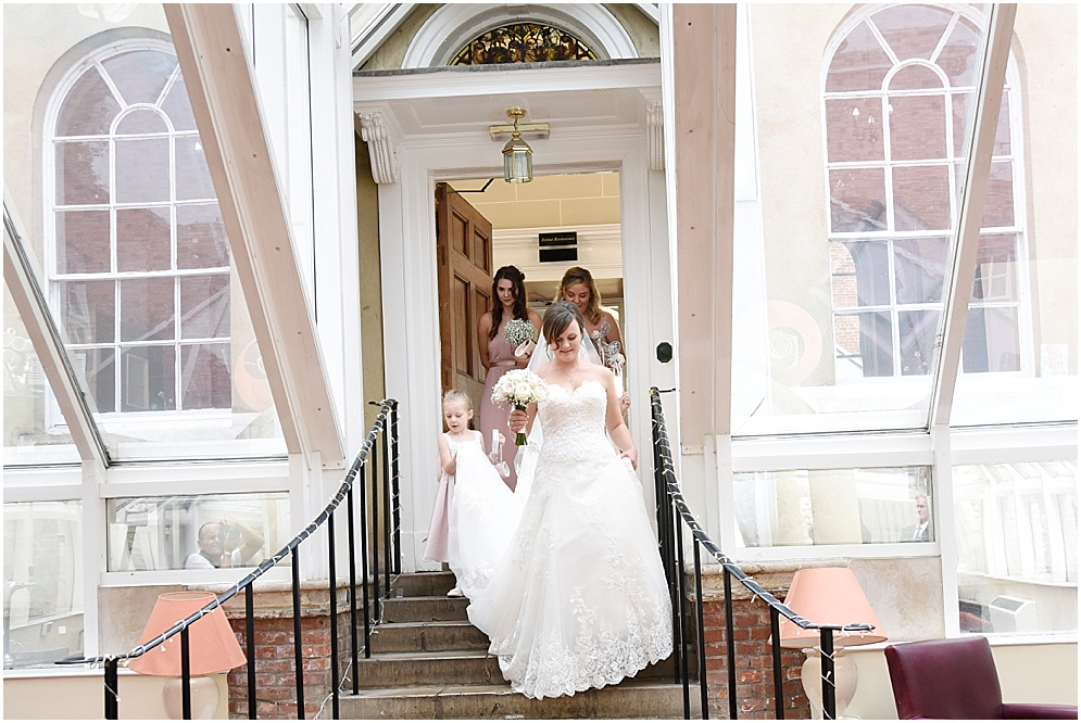 Bride walks down the stairs to meet her dad.
