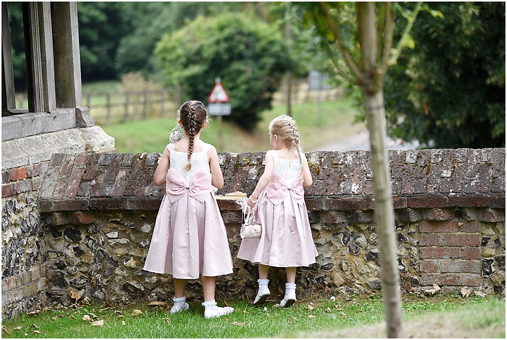 Bridesmaids wait for the bride to arrive at St Nicholas Church. Hitchin wedding photographer.