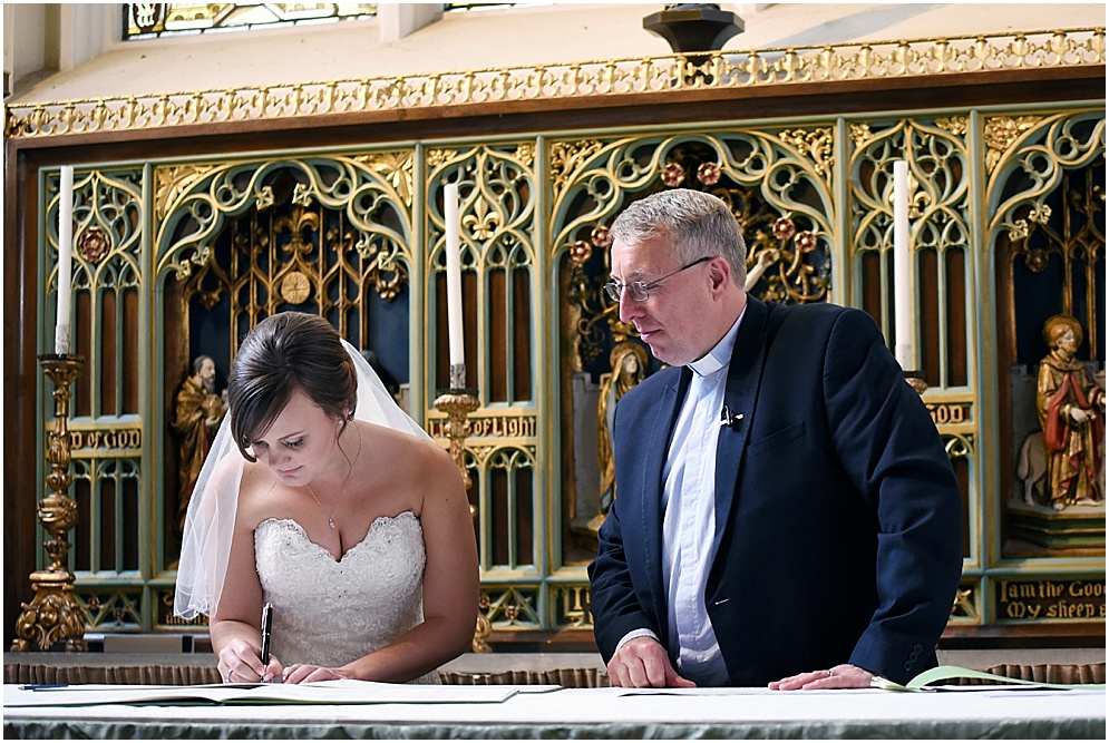 Bride signing the register in church.