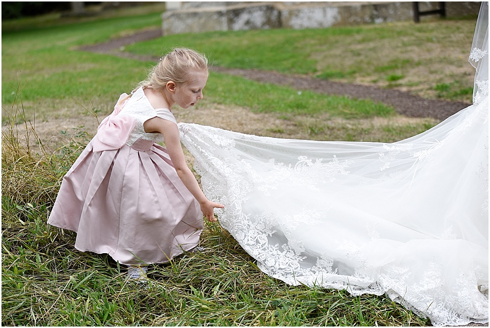 Flower girl helps the bride with her veil on her wedding day.