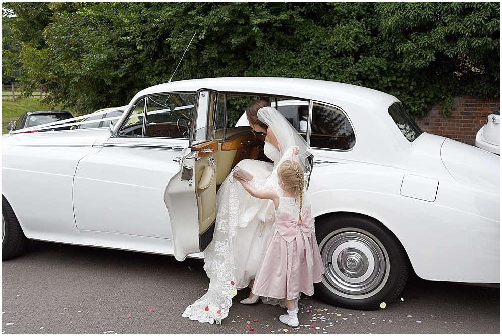 A bridesmaid helps the bride get into the wedding car in Hertfordshire..