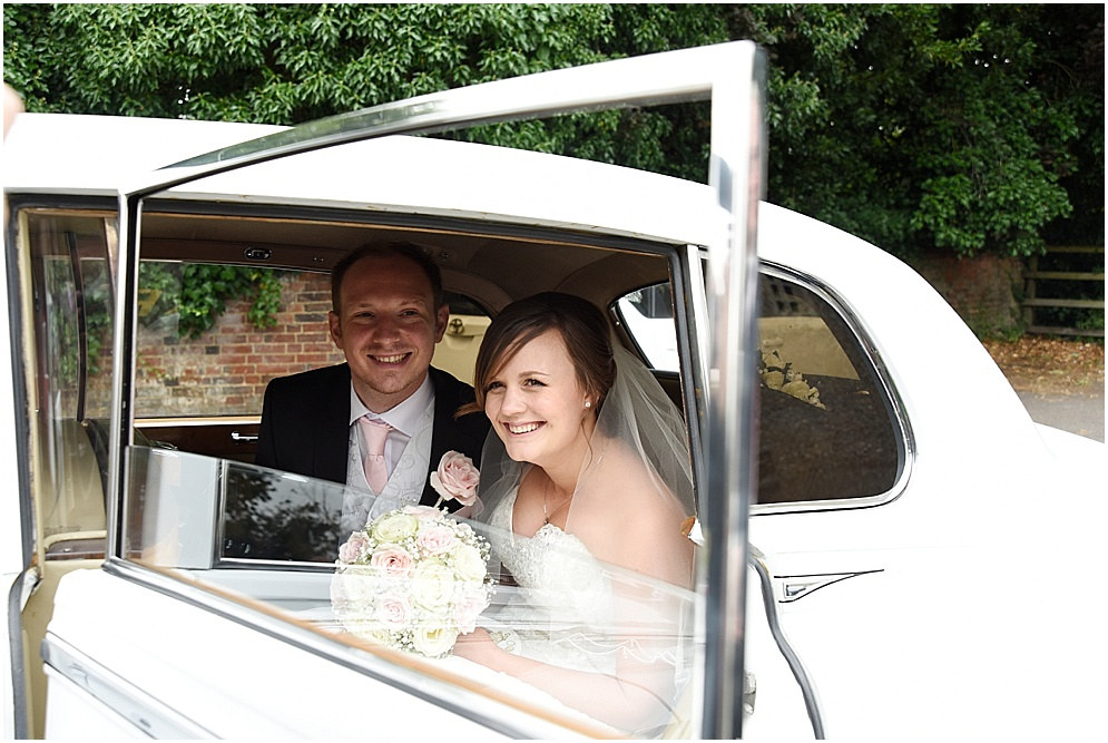 Bride and groom pictured in their wedding car. Hitchin Priory wedding photography.