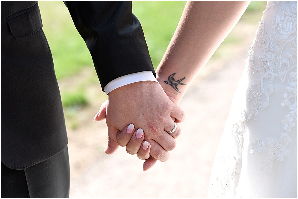 Close up photograph of a bride and groom holding hands.