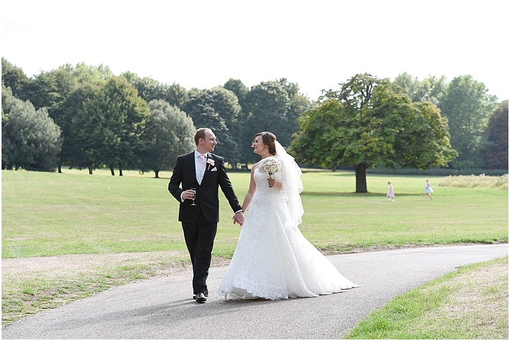 Wedding at Hitchin Priory, a bride and groom walk across the lawn.
