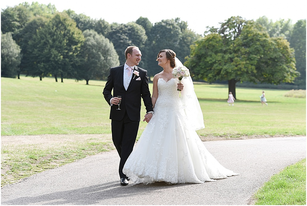 Bride and groom walk hand in hand across the lawn on their wedding day. Hitchin Priory wedding photography.