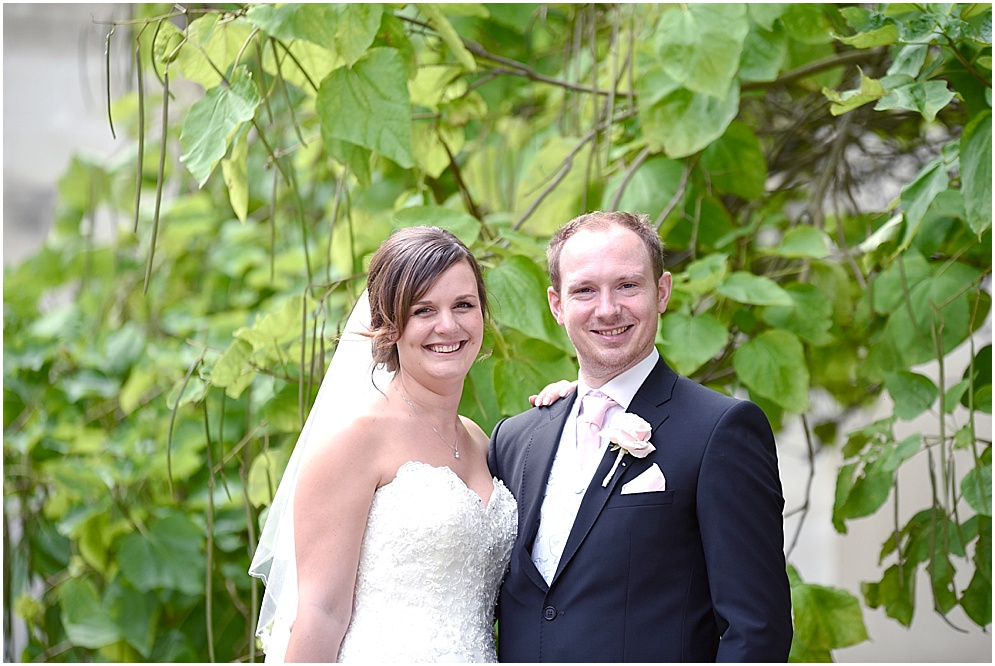 Bride and groom pictured smiling on their wedding day at Hitchin Priory.