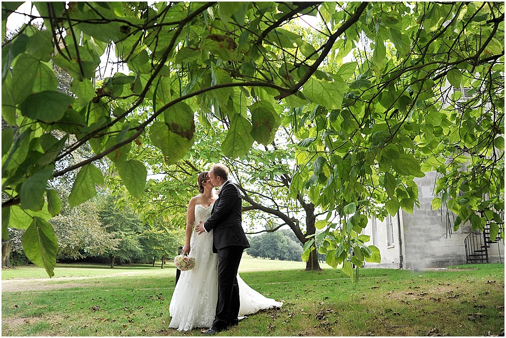 Hertfordshire wedding photographer. Bride and groom pictured beneath a tree.