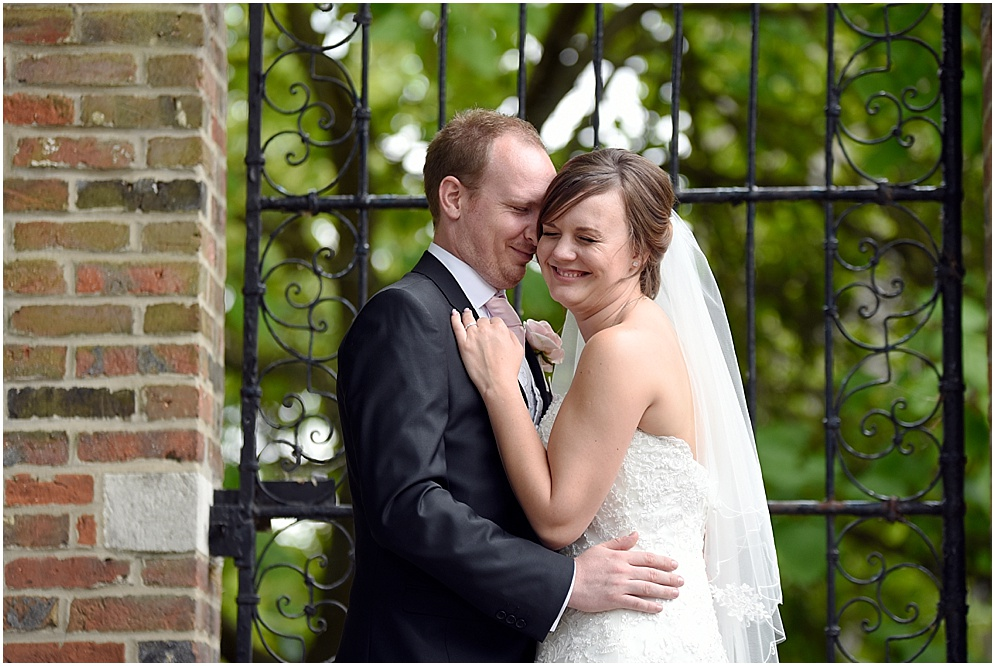Bride laughs with the groom on her wedding day at Hitchin Priory in Hertfordshire.