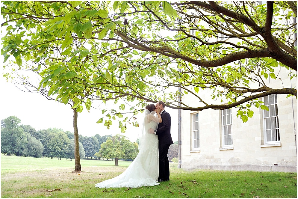 Hitchin Priory wedding photography of a bride and groom sharing a kiss underneath a tree.