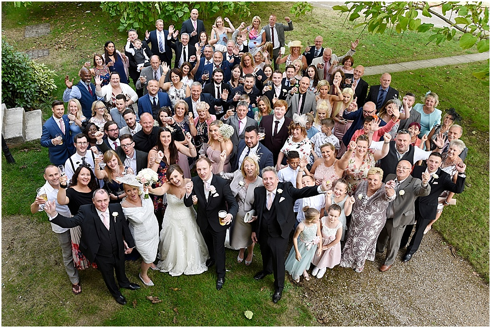 Group photograph of a bride and groom with all their wedding guests.