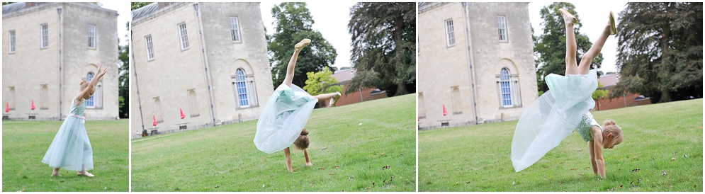 Flower girl does cartwheels across the lawn at a wedding at Hitchin Priory in Hertfordshire.