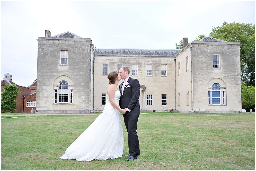 Weddings at Hitchin Priory. Bride and groom hold hands on the venues lawn.