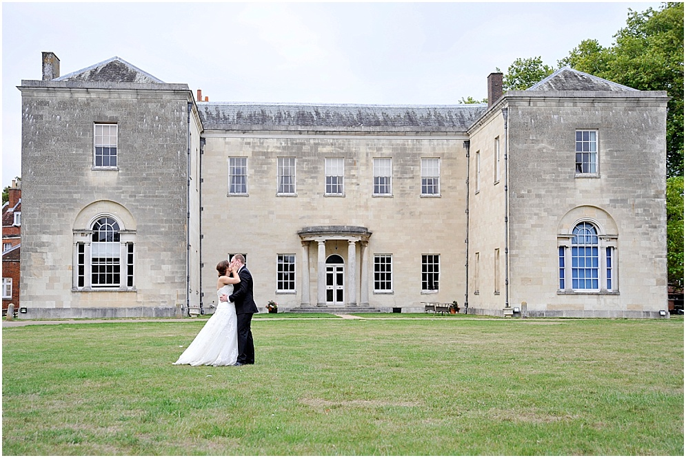 Bride and groom share a kiss on their wedding at Hitchin Priory in Hertfordshire.