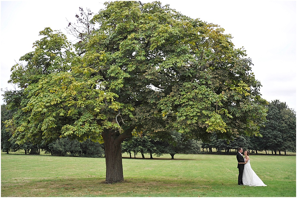 Wedding at Hitchin Priory. A bride and groom pictured by the tree in the grounds.