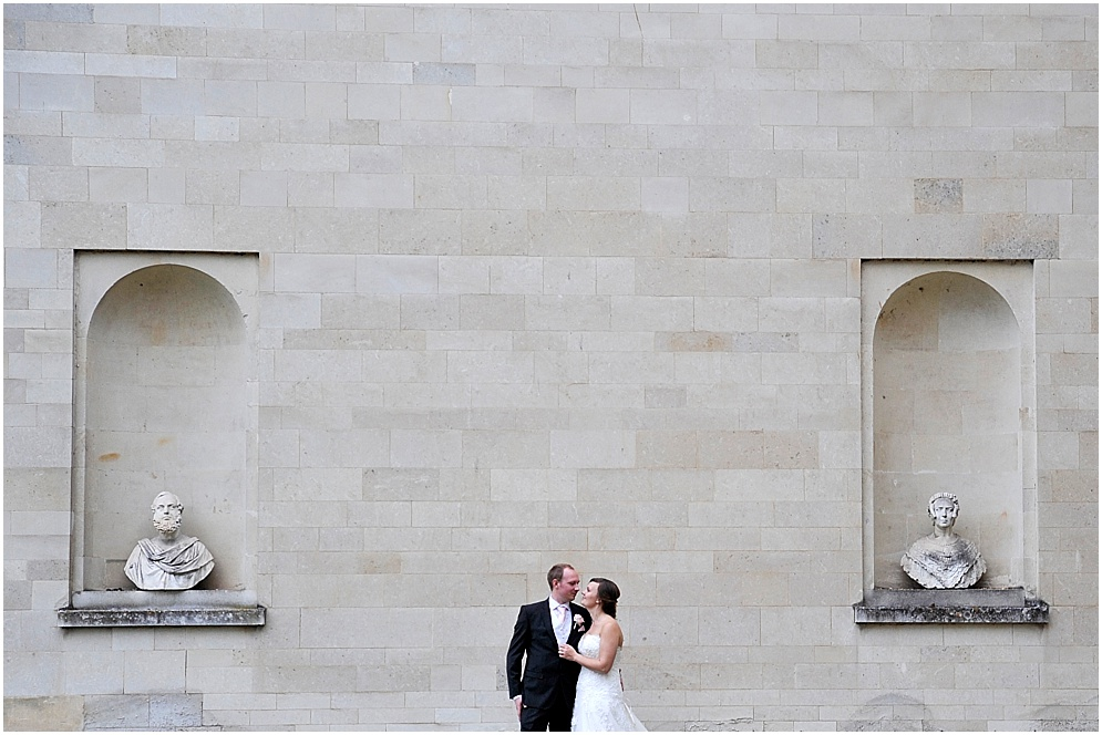 Portrait of a bride and groom by the statues. Hitchin Priory wedding photographer.