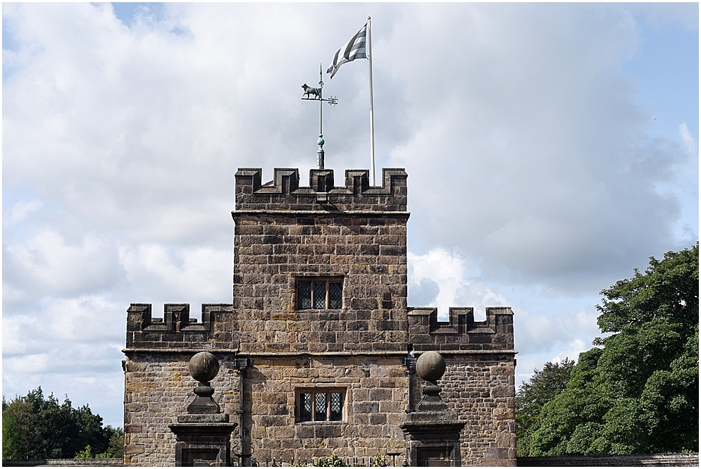 The flag flies high against the blue sky from one of the towers at Hoghton Tower in Lancashire.