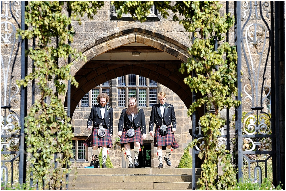 Groomsmen walk through the courtyard of Hoghton Tower. Wedding photography in Lancashire.